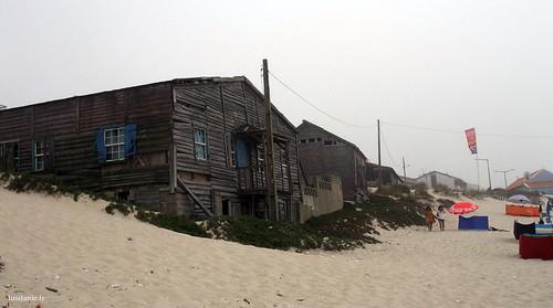 Casas de madeira em ruínas à beira mar, na areia