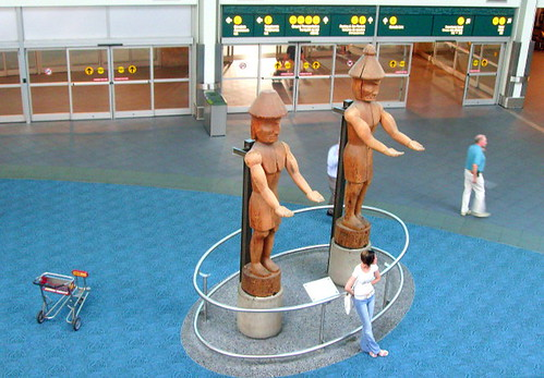 Four Host First Nations (FHFN) wooden figures at the YVR airport
