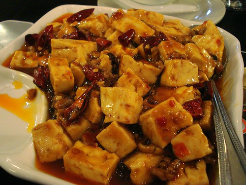 Close-up on a dish of soft tofu cubes in an oily red sauce with pieces of dried red chillies visible.