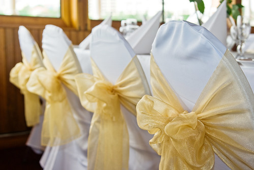 Chairs Covered in White and Decorated with Gold Bows for a Wedding Reception