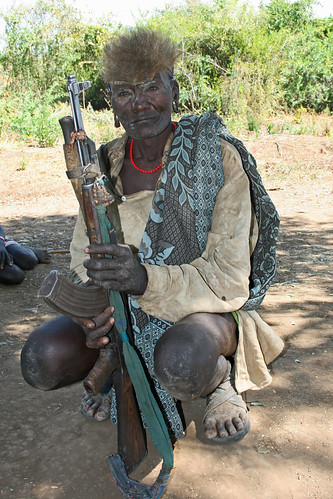 Tribal views: the Mursi: man with an AK-47; the hair natural or a wig