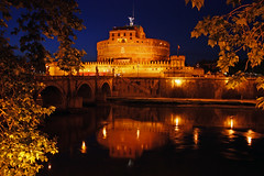 By the Tiber (Rich007) Tags: bridge blue light italy orange pope vatican rome roma tree castle water leaves yellow architecture night river dark lights evening michael leaf audreyhepburn roman fort goth tosca tiber baroque fortress archangel hadrian romanempire emperor goths castelsantangelo lazio saintpeters puccini archangelmichael romanholiday gregorypeck papal bridgeofangels alaric stpetersbasillica rivertiber tiberriver benvenutocellini ponsaelius giacomopuccini mausoleumofhadrian emperorhadrian passettodiborgo