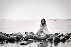 Seafaring Siren. (The Vision Beautiful) Tags: sea portrait blackandwhite bw lake film water girl sailboat rocks magical rockwall whitedress katyeskillman