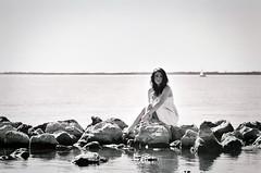Seafaring Siren. (The Vision Beautiful) Tags: sea portrait blackandwhite bw lake film water girl sailboat rocks magical rockwall whitedress katyeskillman