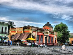 The new municipal market (peggyhr) Tags: blue trees brazil sky orange white green yellow clouds weeds waterfront patterns textures sidewalk palmtrees colonialarchitecture shops balconies pr colourful peelingpaint umbrellas handicrafts decadence awnings cafes paranagu oldsection wroughtironrailings kriskroscontacts peggyhr newmunicipalmarket archedfrenchwindows 1296fa cobbledplaza takenwithcanonpowershotsd880is