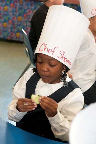 Chef Shania, a student, enjoys a healthy cucumber at the Chefs Move to Schools event.