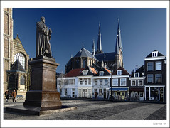 Delft Postcards: Hugo Grotius... at Market Square! (B'Rob) Tags: city travel bridge blue light snow streetart holland color bird art tourism church water bike bicycle statue azul architecture night square photography canal photo yahoo google arquitectura nikon flickr picture nederland thenetherlands ciudad tourist colores best explore cielo hugo polarizer estatua 1224mm kerk mejor tradicin zuidholland nieuwekerk d40 brob explored crotius brobphoto