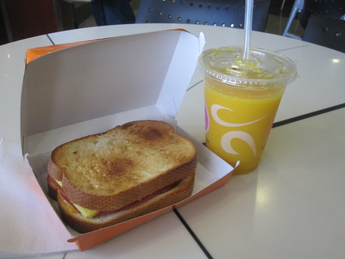 egg and bacon sandwich, orange juice at airport café - $11.25