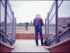Taking Scores (Bentbarbie) Tags: blue usa mamiya hat lines speed america fence ball 645 cowboy university baseball crowd slidefilm chain jeans pro epson natalie ektachrome leading oklahomacity naia 220 umpire scores ocu e100s 6x45cm bentbarbie scanv500