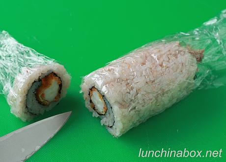 Cutting the fried shrimp sushi roll