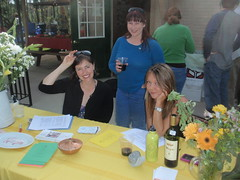Members: Jane (smiling) and Alyssa signing in diners as Heather oversees