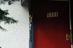 11:11 the prayer door (Gem  Salsberg) Tags: reddoor doorway om windchime 1111 intensecolour vancouverbccanada brasslock cedarbranches whitestucco prayerdoor gemsalsbergphotos nearcommercialdrivevancouverbc eastvancouverhouse