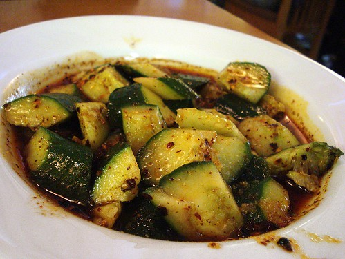 A dish of skin-on cucumber pieces bathed in a dressing of red-coloured chilli oil, with plenty of ground Sichuan pepper.
