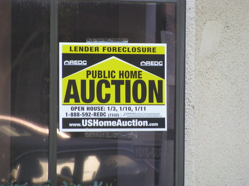 An auction sign in the window of a house after foreclosure