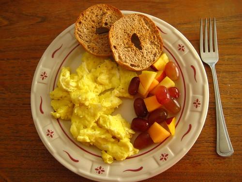 scrambled eggs, bagel, fruit salad