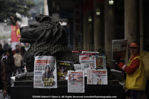 CHinese girl sales newspapers in front of the Bus Terminal with