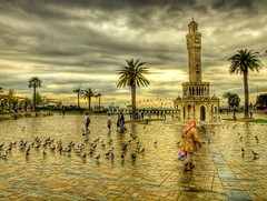 Feeding the pigeons in the rain .. (Nejdet Duzen) Tags: trip travel bird tower clock rain turkey square feeding pigeon trkiye clocktower saat palmiye konak soe plam izmir ku gvercin kule meydan turkei seyahat yamur saatkulesi besleme abigfave ~~api~~