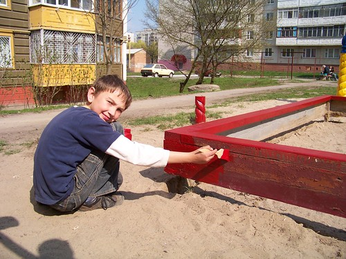 Maxime painting the sand box