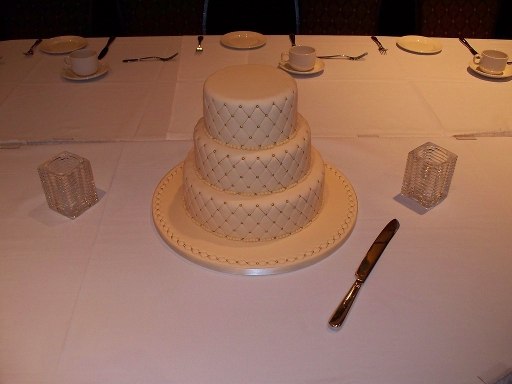 Diamond embossed ivory wedding cake with gold sugar bead details