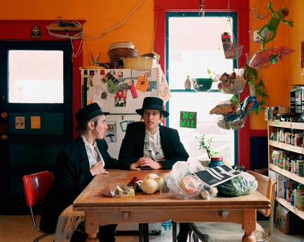 "Two male Orthodox Jews sit a kitchen table. One is staring straight at the camera. The other reaches out their hand to the other while gazing at them. There is a ""no war"" sticker on the window."