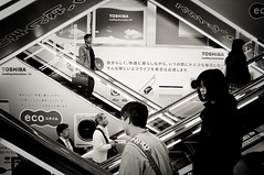 Escalator Antics (kaoni701) Tags: camera travel people bw white black japan contrast japanese tokyo store nikon asia technology tech escalator places electronics  akihabara 28 60mm gadget tones nihon dx yodobashi electrictown d90  shoppingjapan tamorn worldsbestnikonshots