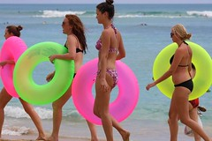 girls in bikinis with inflatable tubes, waikiki