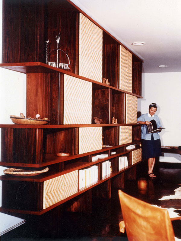Charlotte Perriand reads a book in the background while leaning against a large, boxy but beautiful wooden bookcase and shelving unit