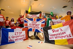 Anti-aviation campaigners with the flags of the other protesting nations join together at Heathrow Terminal One to demonstrate against the 3rd runway and aviation expansion. by Euroflashmob Heathrow and Europe