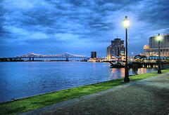 New Orleans Evenings (` Toshio ') Tags: longexposure bridge lamp grass night clouds buildings river lights evening louisiana cityscape nightshot path walk south neworleans riverfront bluehour southeast lightpost riverwalk crescentcityconnection toshio lightedbridge mywinners aplusphoto mississippiriverfrenchquarter heritage2011
