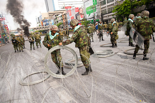 Soldiers unrolling barbed wire along Rama IV, Bangkok