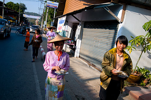 Distributing khao ya koo, sweet sticky rice, on the streets of Mae Hong Son