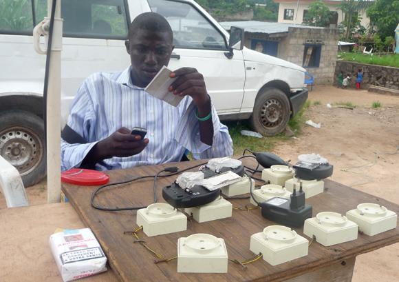 Un jeune patron d'une cabine téléphonique de rue avec son dispositif de chargement de téléphones portables