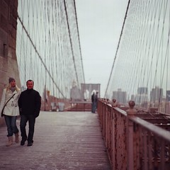 Sightseeing (Inside_man) Tags: wood winter people newyork slr 120 6x6 film colors mediumformat rust couple bokeh manhattan sightseeing citylife tourist brooklynbridge railing strolling bronicas2 pedestrianwalkway por
