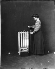 Woman repairing hot water radiator, 1909 (Muse McCord Museum) Tags: mccordmuseum musemccord canada womensday mujeres trabajofemenino radiadores woman standing repair radiator 1909 stripes commons:event=commonground2009 1900s twentieth century 20th tools negativespace