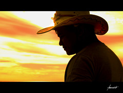 The Cowboy and The Sun (Tomasito.!) Tags: boy shadow portrait sky sun sunlight mountain man guy art beach beautiful smile hat silhouette dedication yellow clouds photoshop photo mac nikon cowboy sundown spirit country philippines picture explore cap marlboro rodeo cowboyhat frontpage cory filipinas courage aquino tomasito brokeback d90 yellowsky cowboypicture 18105mm nikond90 pinoykodakero