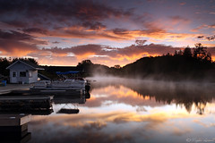 Fire In The Sky (Megan Lorenz) Tags: morning autumn sky mist lake ontario canada fall nature water fog clouds sunrise reflections landscape outdoors dock scenery colorful view vibrant scenic getty gettyimage singhray the4elements abigfave theunforgettablepictures meganlorenz vosplusbellesphotos mlorenzphotography nearalgonquinprovincialpark