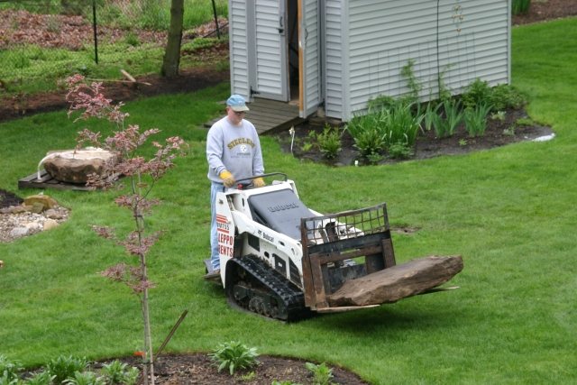 jeff on the bobcat moving a big rock