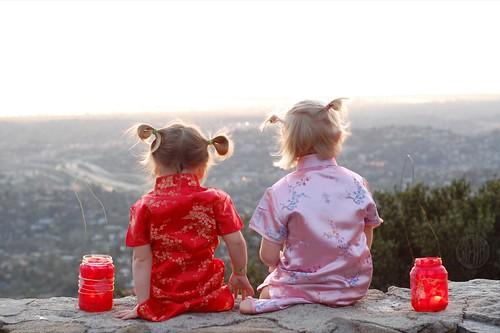 two little geisha girls sitting on a wall...
