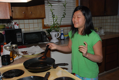 The Child cooks bacon