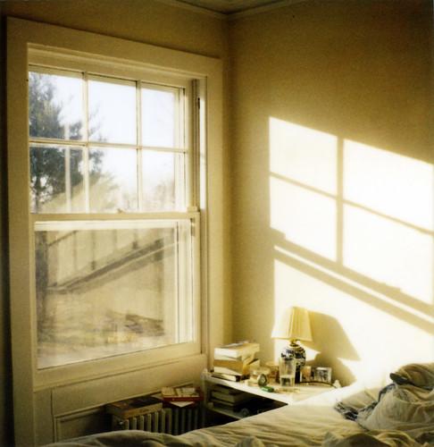 Fotografía de un dormitorio al que le entra luz clara por una enorme ventana