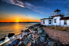 Rocky Driftwood Lighthouse (Surrealize) Tags: ocean seattle park blue roof light sunset red sea sky orange lighthouse mountain beach water birds clouds point evening washington nikon rocks dusk seagull pebbles driftwood magnolia pugetsound fullframe fx brilliant hdr discoverypark olympicmountains 14mm 9exp d700 westpointlight surrealize vegarotatingbeacon