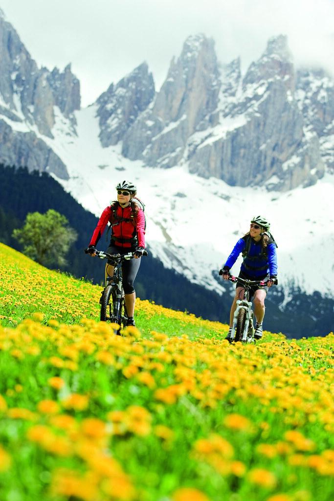 Two women mountain bikers in spring flowers