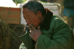 Chinese man puffing on a cigarette