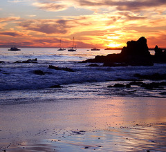 Corona del Mar Sunset (Marcie Gonzalez) Tags: ocean california county ca pink blue sunset shadow red sea sky orange cloud sun reflection beach wet water yellow rock del clouds sailboat canon reflections boats photography lights coast boat mar sand rocks waves afternoon shadows purple bright crash peach blues sunsets newportbeach southern coastal corona newport shore foam beaches coastline peaches oranges gonzalez oceans orangecounty sailboats yellows reds shores marcie pinks seas crashing purples supershot marciegonzalez marciegonzalezphotography