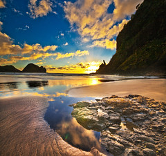 Piha Sunset (Nazar's Collection) Tags: blue newzealand mountain reflection water yellow clouds ground auckland sunrays waitakere piha pihabeach