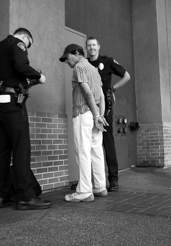 police smile while arresting man in handcuffs
