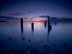 Puget Sound Sunset (Tyler Westcott) Tags: seattle longexposure blue sunset beach water night clouds evening waterfront dusk explore shore pugetsound pilings bluehour goldengardenspark nd400 ndgrad nikond90 hitech06he