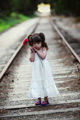 Her Favorite Flower (Extra Medium) Tags: railroad flower cute girl dress innocent shy pigtails summerdress coy sundress oxnard 3yo nikkor85mm14d vcfair09