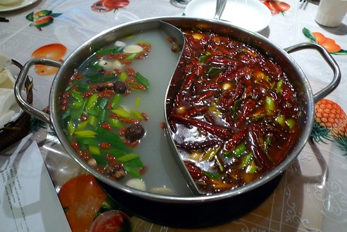 A metal pot divided into two halves down the middle with a curved divider.  One side contains 'medicinal' stock, an opaque light-coloured stock with dried mushrooms, shredded spring onions, and dried reddish berries floating in it.  The other side contains a spicier, oilier stock which is almost completely invisible under the layer of dried chillies floating on top.