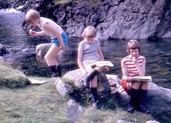 Lunch (theirhistory) Tags: food girl grass shirt river children rocks stream tshirt shorts wellies